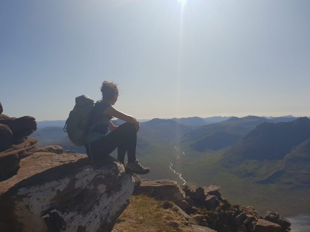 Adventurer Nic sitting to admire the view over to the Fisherfields from the ascent of An Teallach in the north west Scottish highlands