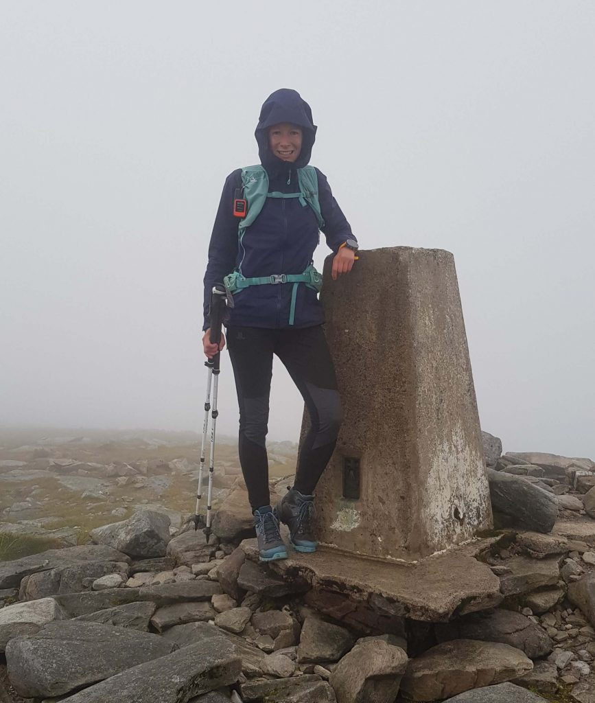 Adventurer Nic standing next to the trig point at the summit of Ben Hope, a Munro in the north of Scotland