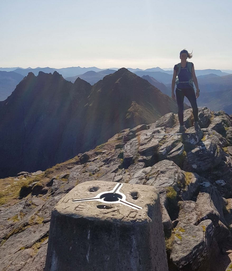 Adventurer Nic on the summit of Bidein A'Ghlas Thuill. A Munro summit on An Teallach in the North West Scottish Highlands