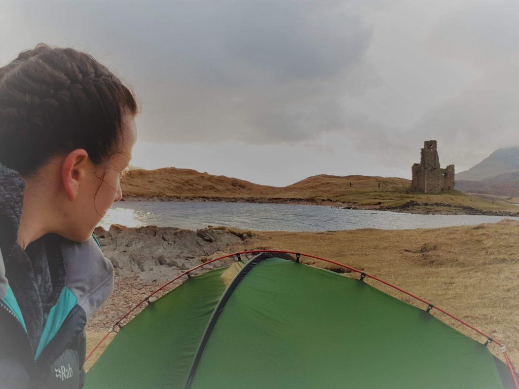 Adventurer Nic during her first visit to Loch Assynt in 2018. She looks over her Terra Nova Southern Cross 2 tent towards Castle Ardvreck