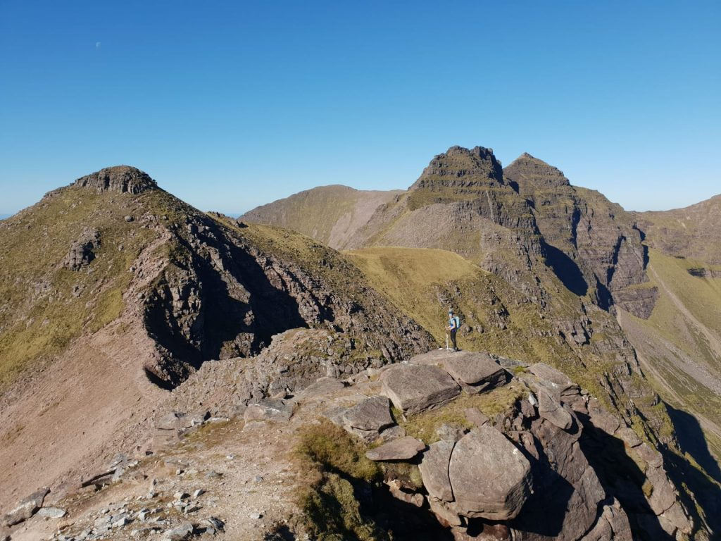 Adventurer Nic is a dot in this photo, standing on a rocky pinnacle on the ascent of An Teallach, a Munro mountain in the remote Scottish highlands