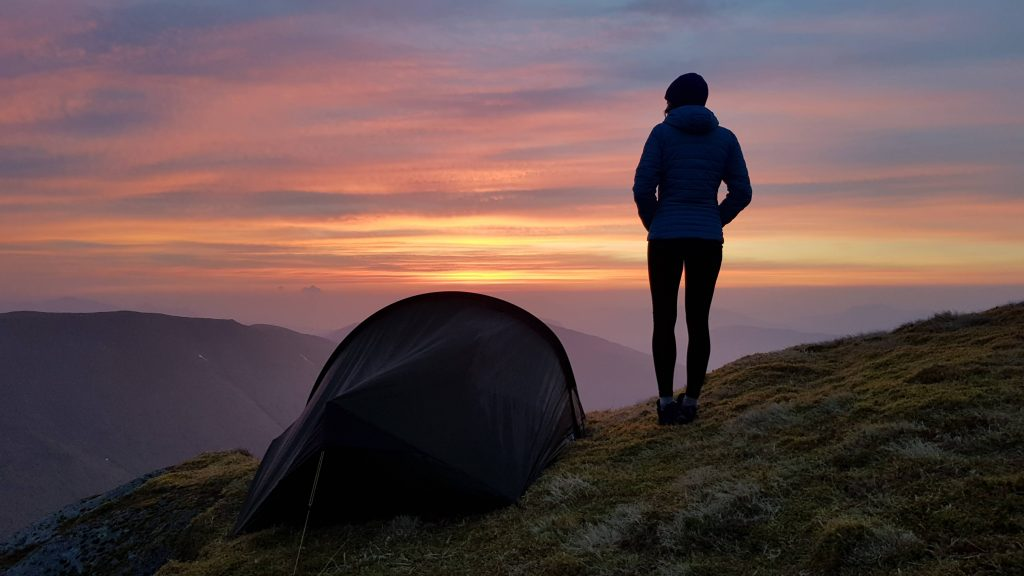 Woman standing next to tent looking at a mountain view at sunrise in the Scottish Highlands