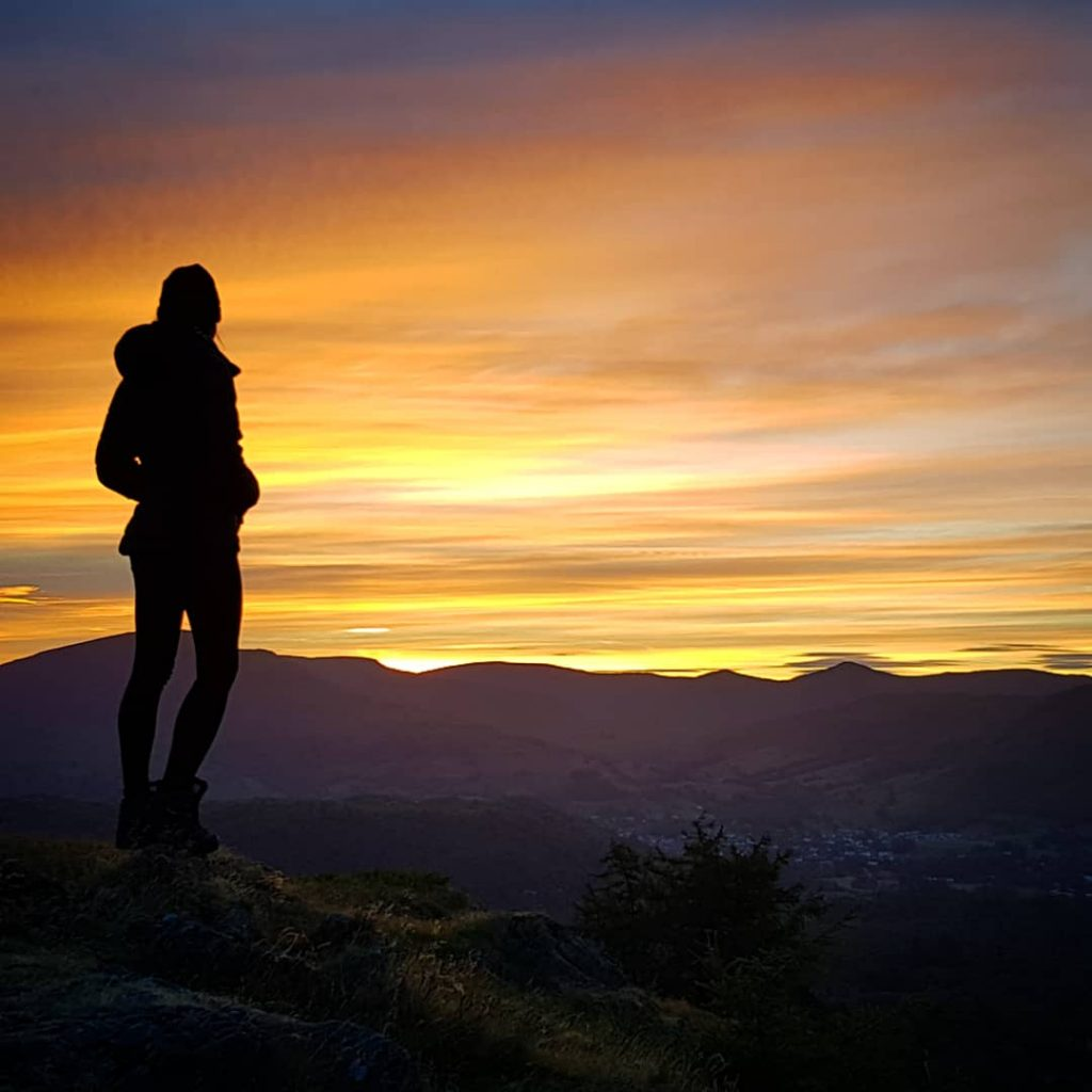 Adventurer Nic standing by her bivvy bag overlooking Windermere from Black Fell at Sunrise
