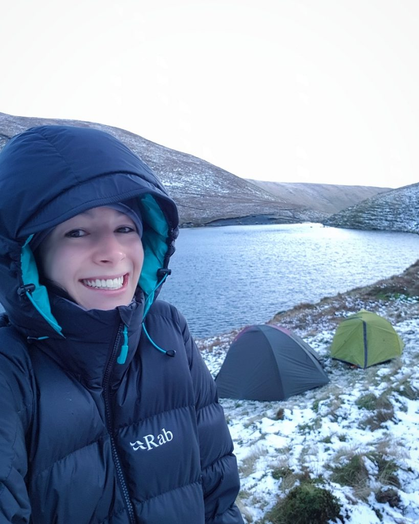 Adventurer Nic standing by her tent at Scales Tarn, Blencathra just after Sunrise in Winter