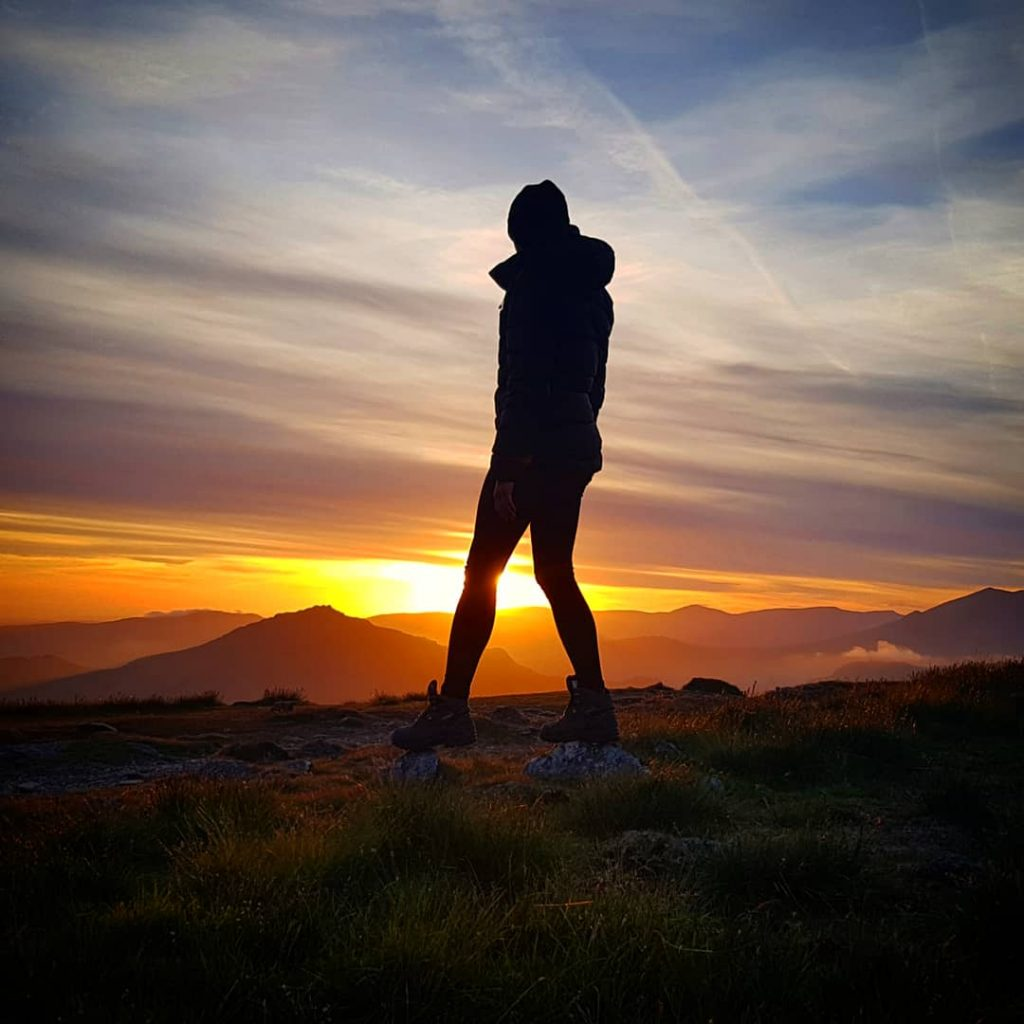 Adventurer Nic by her bivvy bag at sunset on Dow Crag