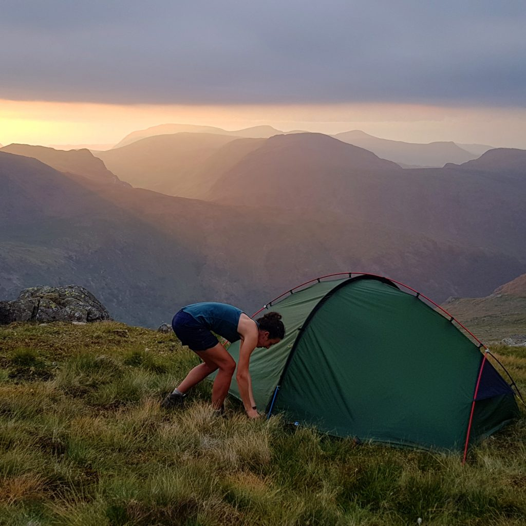 Adventurer Nic getting into her tent at sunset on Glaramara