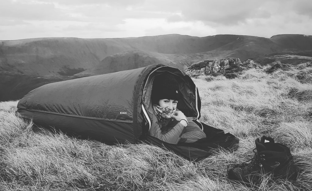 Adventurer Nic in her bivvy bag on Place Fell in black and white