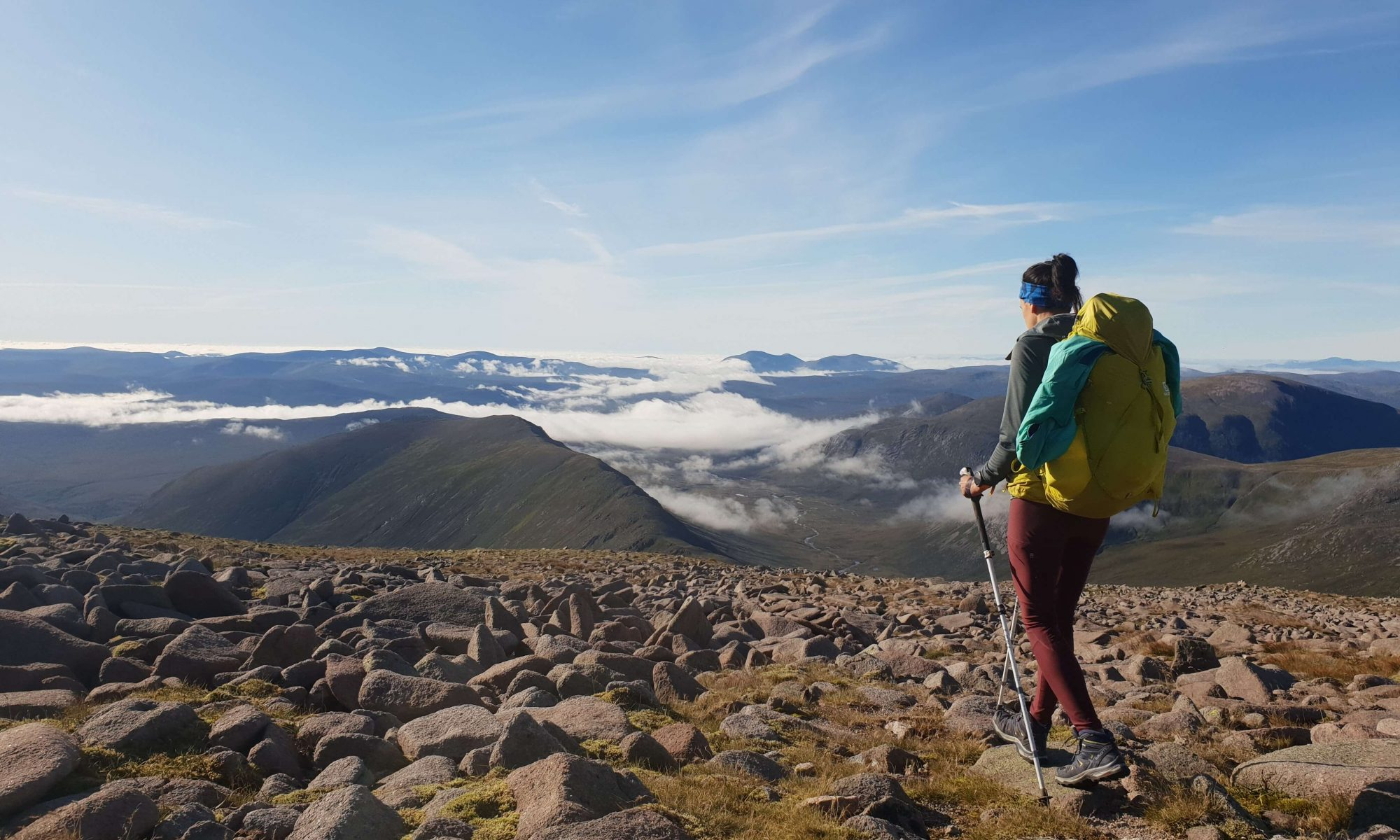 Adventurer Nic walking on the summit of Ben Macdui above a fading cloud inversion