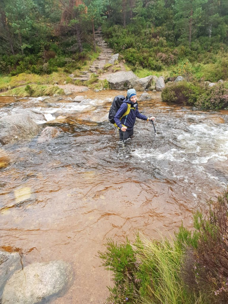 Adventurer Nic amid a thigh high river crossing in the Cairngorms