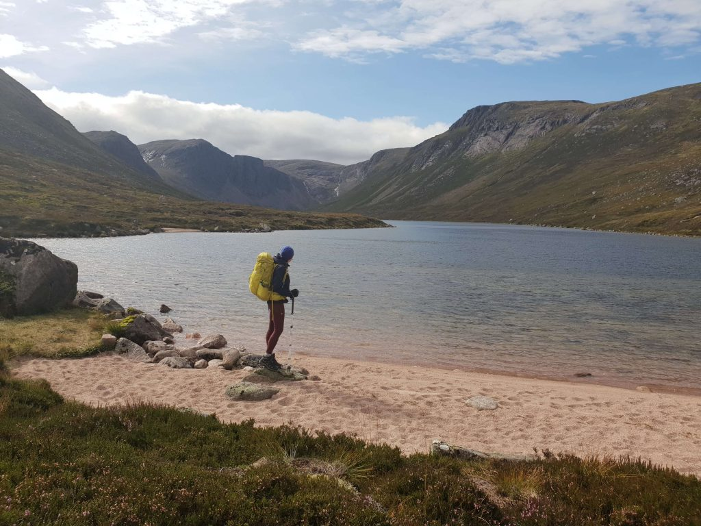 Adventurer Nic standing on the edge of Loch Avon in the Cairngorms National Park
