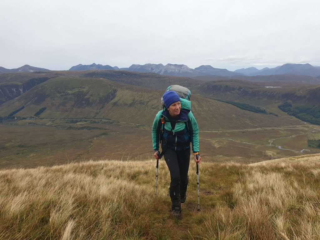 Adventurer Nic ascending Moruisg, a Munro mountain in the Scottish Highlands with the Torridon hills in the distance