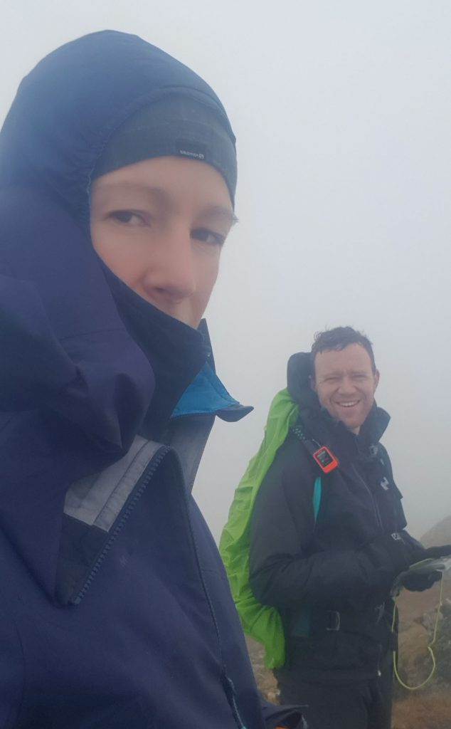 Adventurer Nic and James Forrest on the summit of Bidein a' Choire Sheasgaich looking wet and exhausted