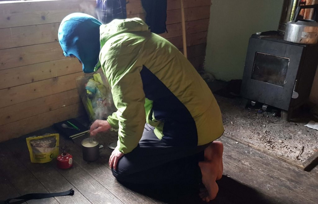 James Forrest making breakfast on the floor of Hutchinson Memorial Hut