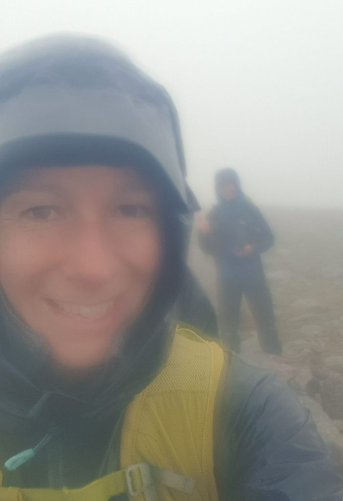 Adventurer Nic and James Forrest pose for a wet summit selfie on Monadh Mor