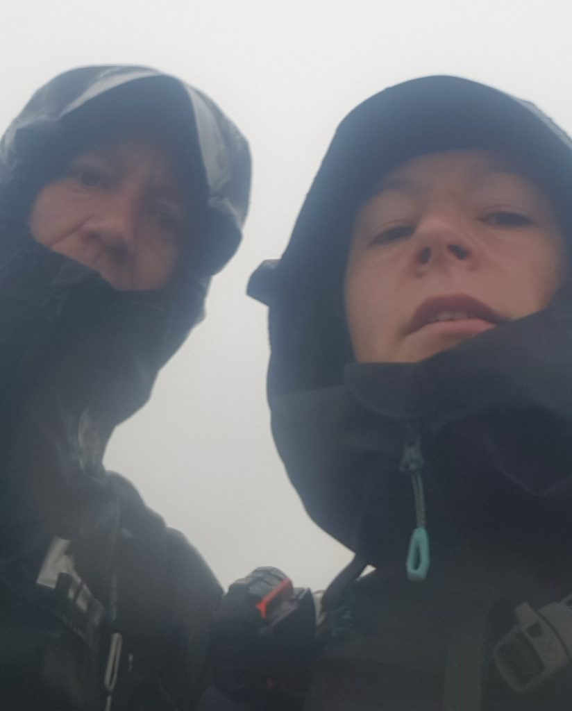 Adventurer Nic and James Forrest on the summit of Sgurr Choinnich looking and feeling like drowned rats