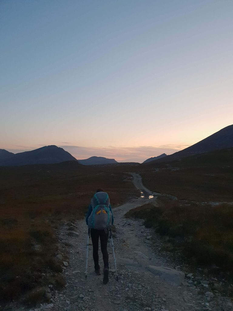 Adventurer Nic walking in towards Shenavall bothy after sunset