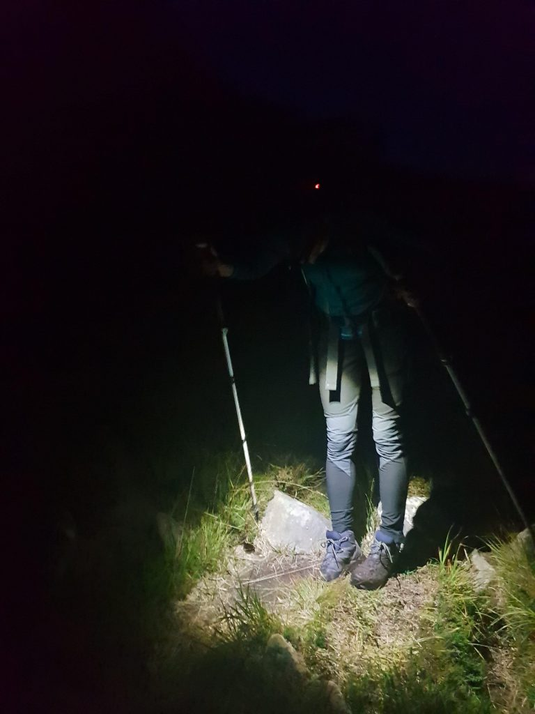 Adventurer Nic looking down at her feet, illuminated by her head torch whilst hiking at night