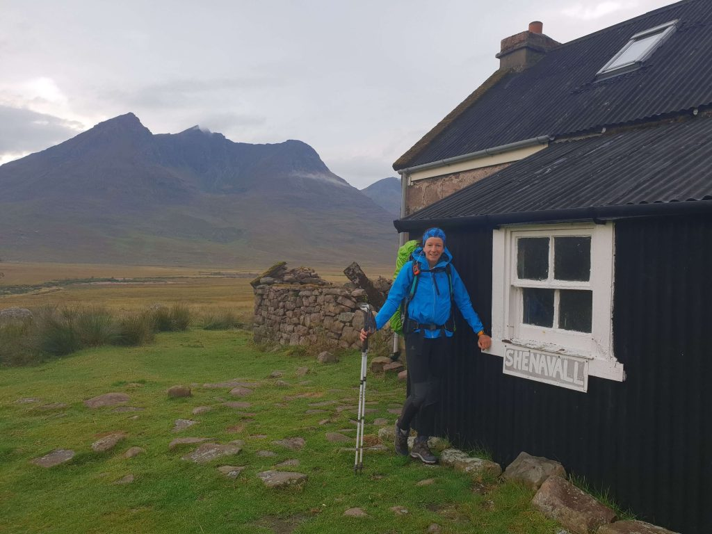 Adventurer Nic standing outside Shenavall Bothy
