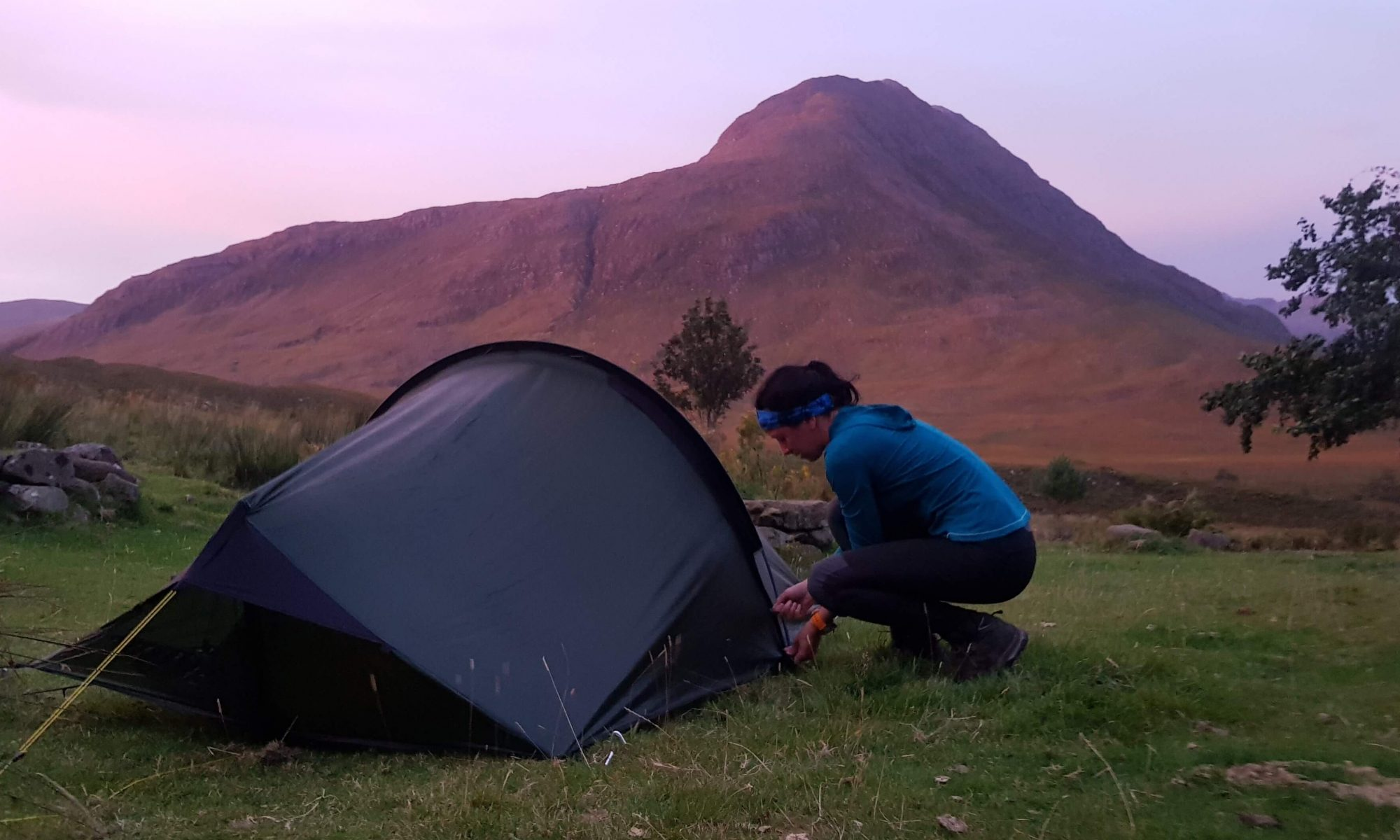 Adventurer Nic zipping down her tent in front of Shenavall Bothy in the Scottish Highlands before setting off to climb the Fisherfield Munros
