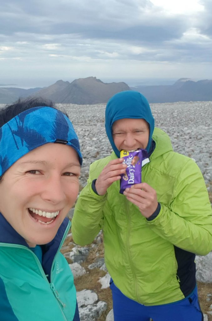 Adventurer Nic with James Forrest eating a bar of Cadbury's Dairy Milk Chocolate on the summit of Sgurr Ban, the first of five Fisherfield Munro mountains