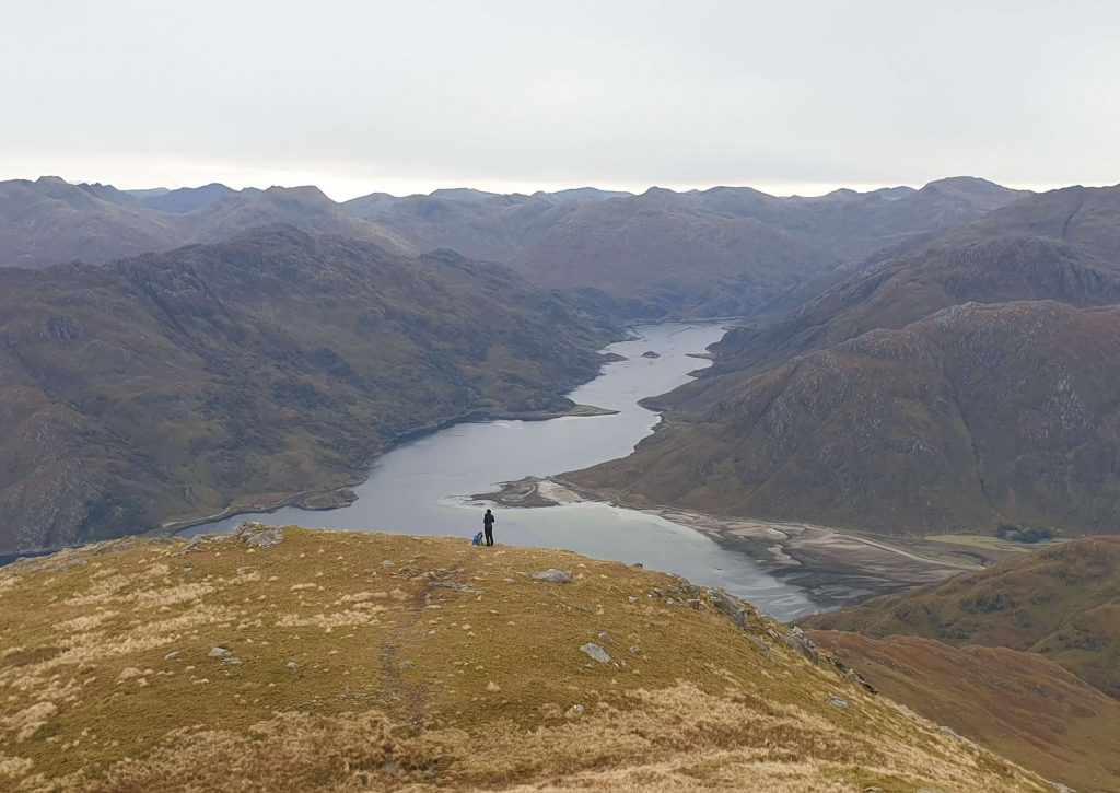 Adventurer Nic waiting for James Forrest on the descent of Ladhar Bheinn overlooking Barrisdale Bay