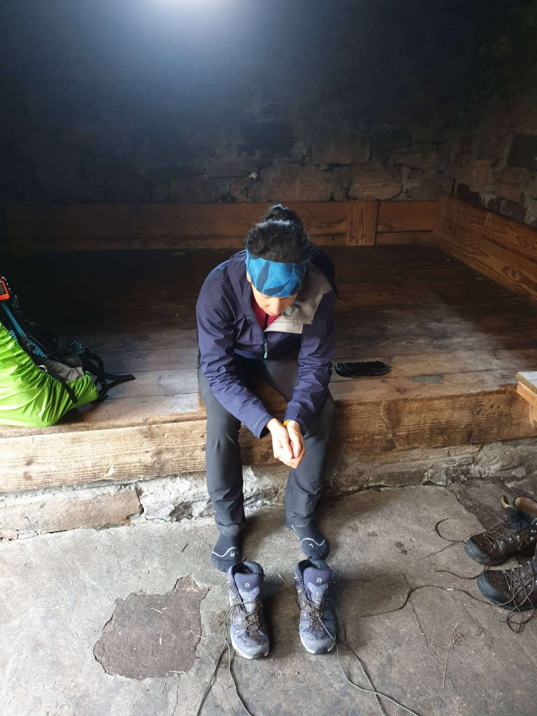 Adventurer Nic painfully contemplating putting her dry feet into wet boots in Sourlies Bothy