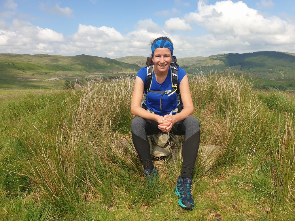 Adventurer Nic sitting on the summit of Lamb Pasture on the Bannisdale Horseshoe, The Lake District