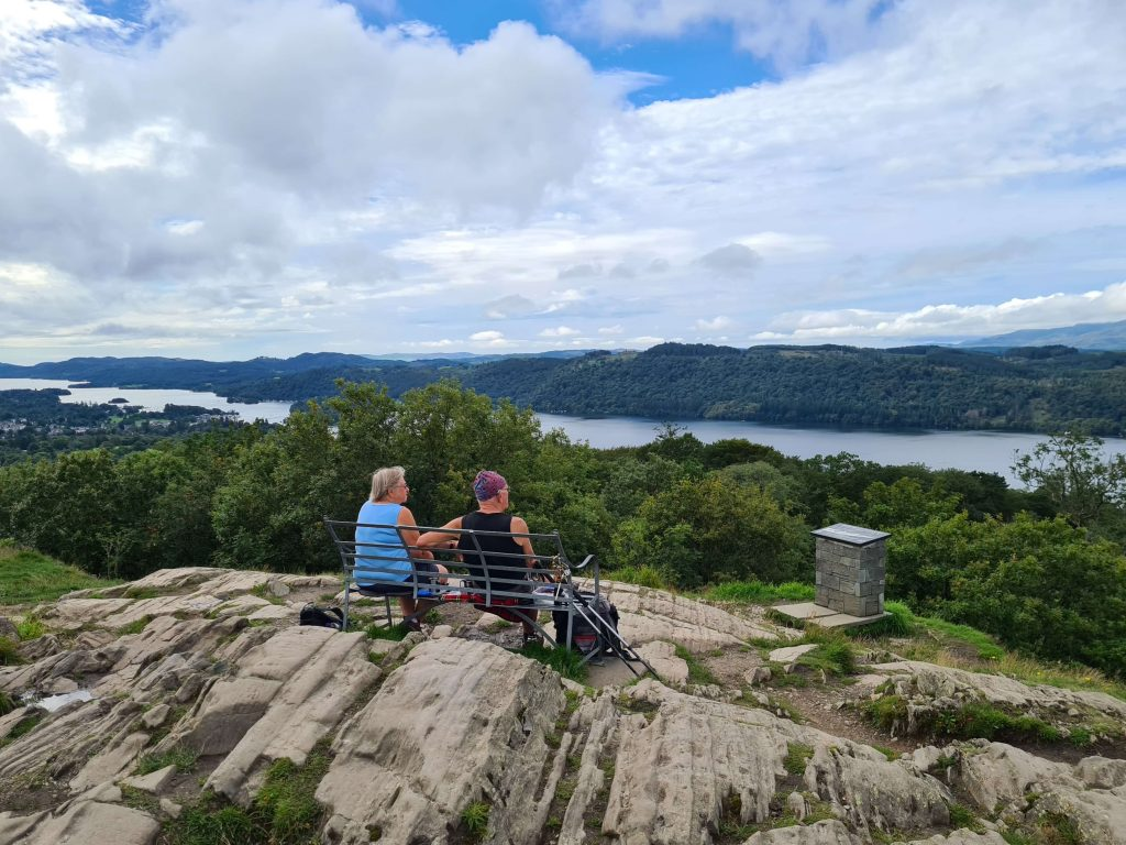 A couple enjoying the view from the bench atop Orrest Head