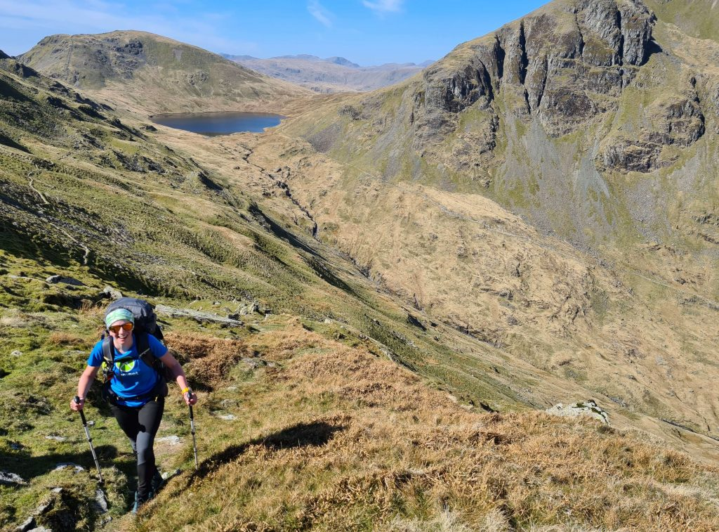 Adventurer Nic walks away from Grisedale Tarn ascending St Sunday Crag