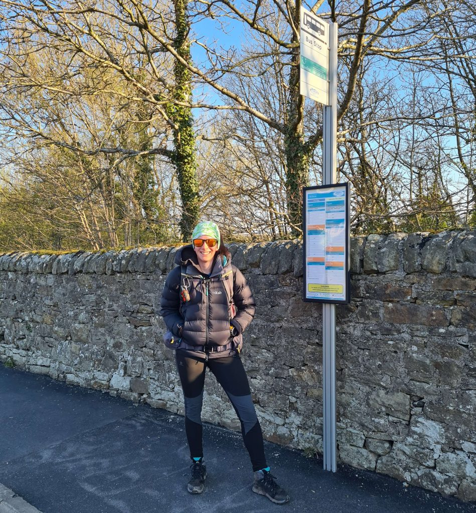 Adventurer Nic stands at her local bus stop in Cockermouth ready to travel the Lake District by bus