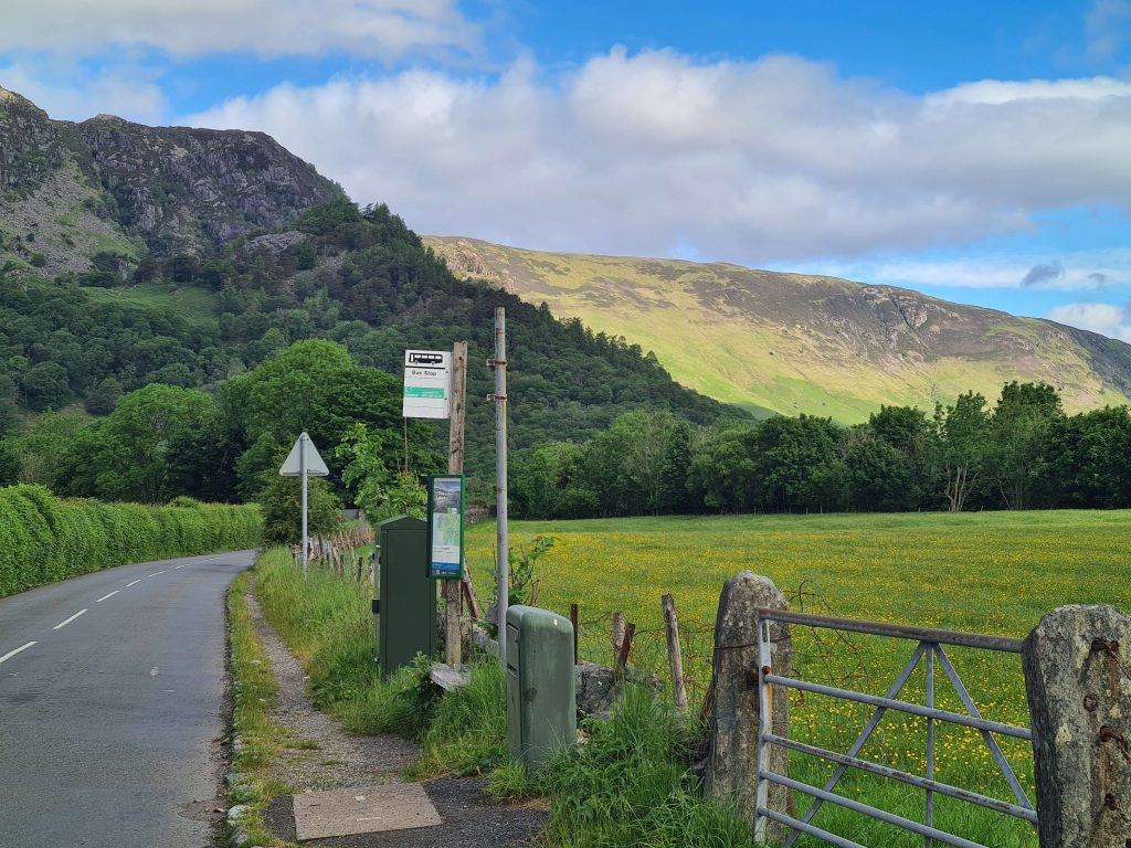 Bus stop in the village of Rosthwaite, the Lake District with fells and farmland in the background