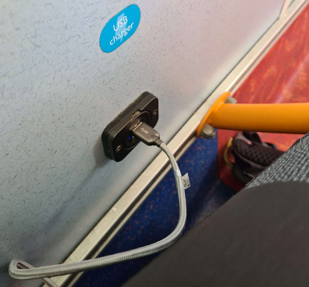 Nic charges her phone using the USB port on the Stagecoach bus