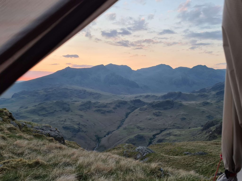 Adventurer Nic peeks out of her tent during a wild camp in Eskdale at sunset